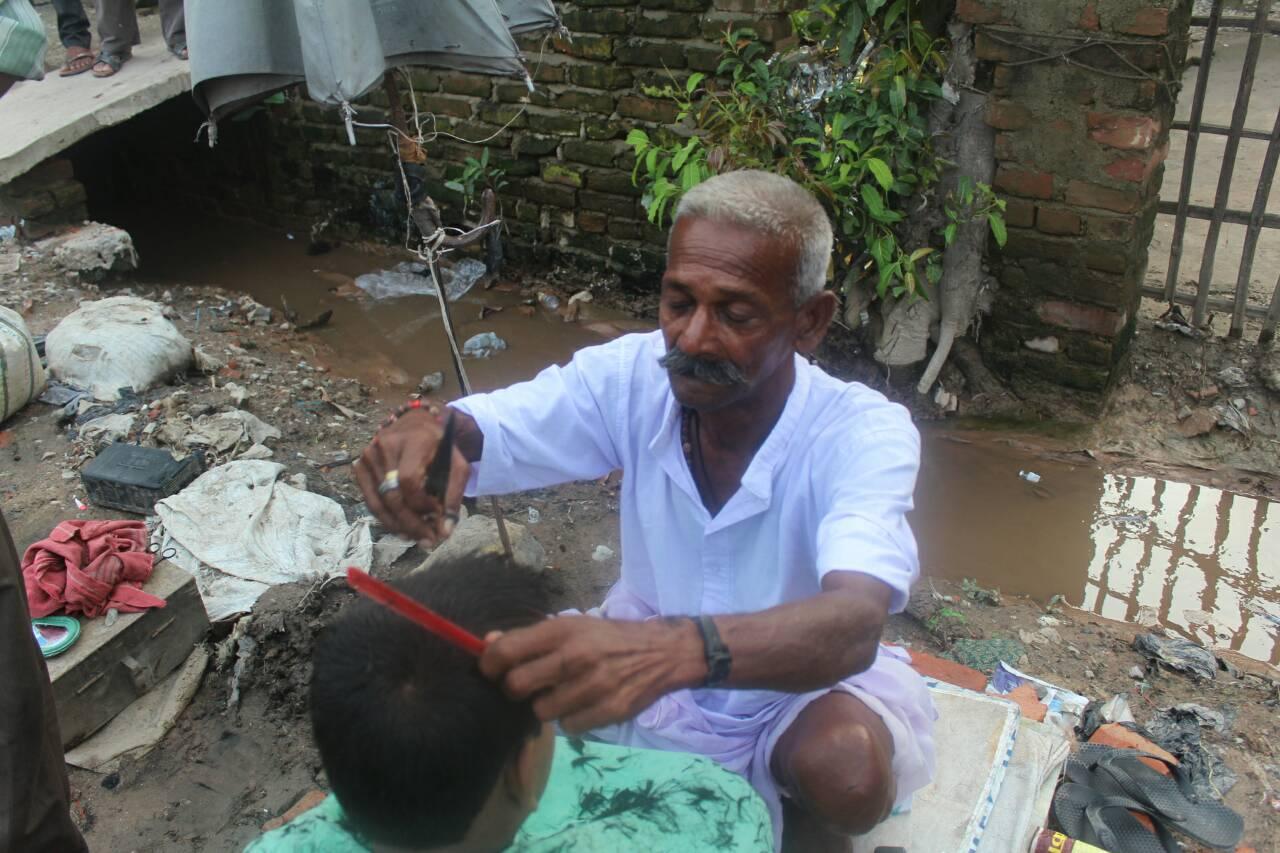 インドの路上でカットするオヤジ。まさに職人技が光る。